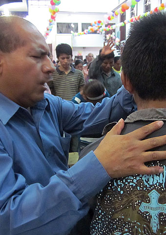 Pastor Antonio Cruz Rodas prays for paritioner in Chiapas, Mexico.